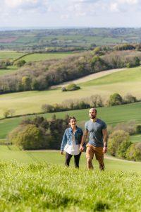 a couple walking through a field